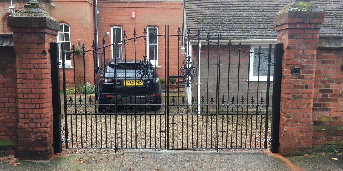 Traditional wrought iron estate gates with a bi folding design