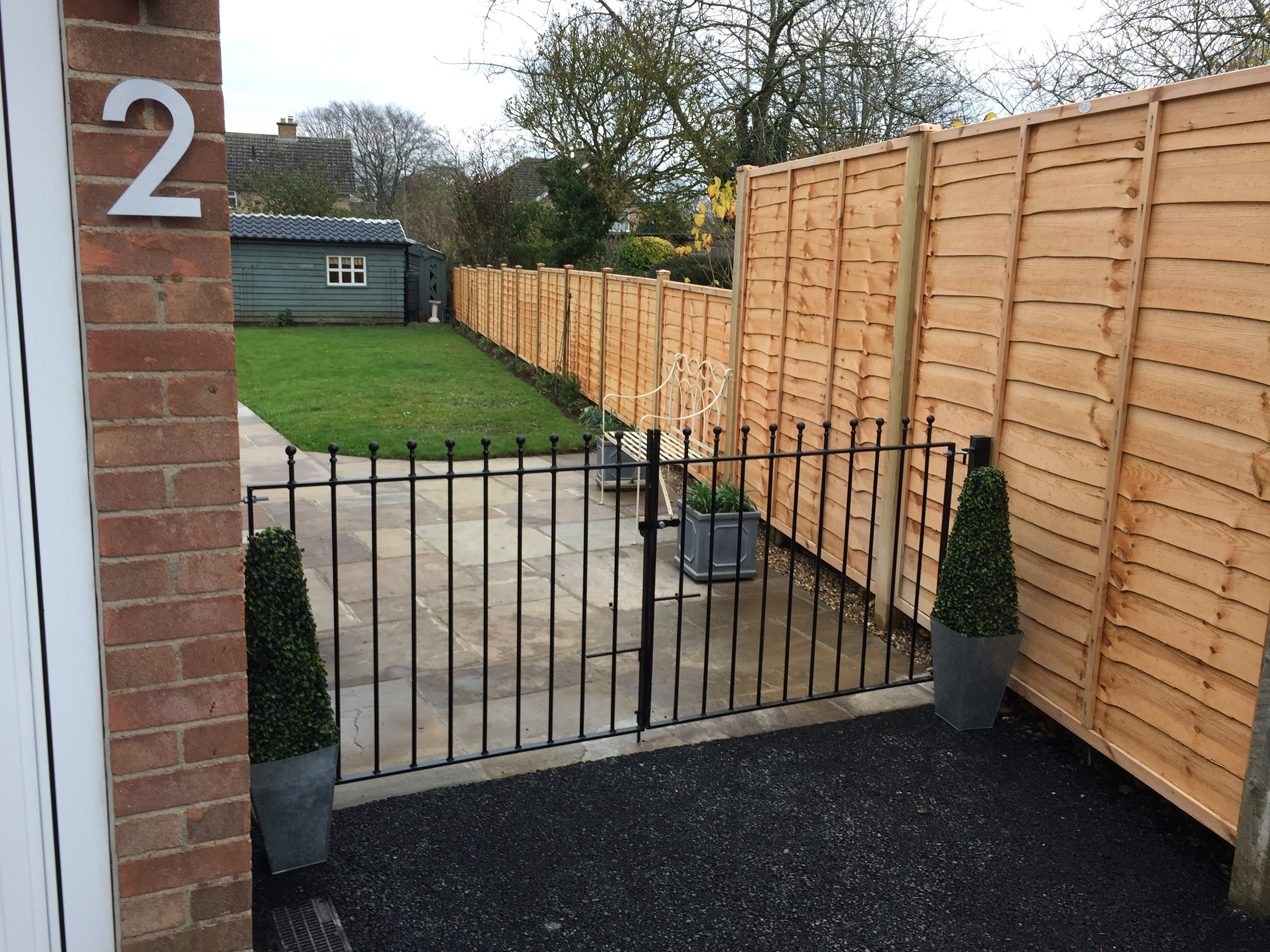 Manor metal driveway gates fitted between house wall and wooden fence panels